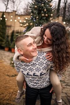 Возле елки стоят женщина и мужчина, они счастливы, новогоднее настроение