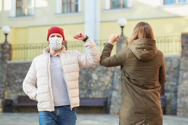 医療マスクをかぶった女性と男性が抱擁で挨拶する代わりに肘をぶつけます