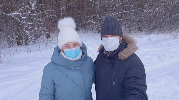 Женщина и мужчина в медицинских масках гуляют в зимнем парке, ношение медицинской маски в общественных местах помогает предотвратить развитие эпидемии коронавируса