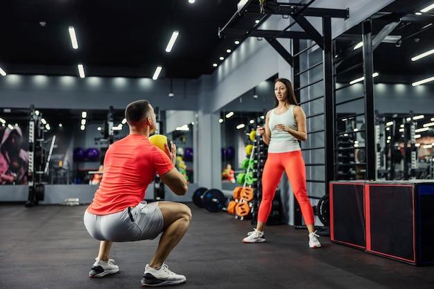 スポーツウェアを着た女性と男性がジムでフィットネスボールを投げます。男はしゃがんだ姿勢で、直立している女の子にボールを投げる準備をしています。スポーツチャレンジ、カップルゴール