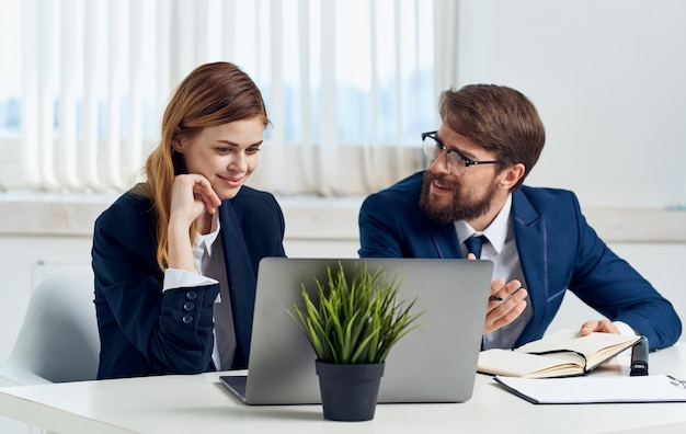한 여자와 정장을 입은 남자가 노트북 모니터와 냄비에 꽃을 배경으로 본다. 고품질 사진