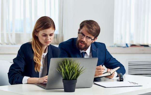 한 여자와 정장을 입은 남자가 노트북 모니터와 냄비에 꽃을 본다.