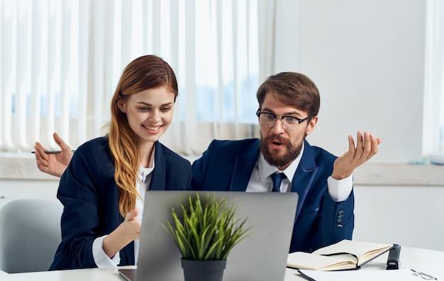 Женщина и мужчина в костюмах смотрят на монитор ноутбука