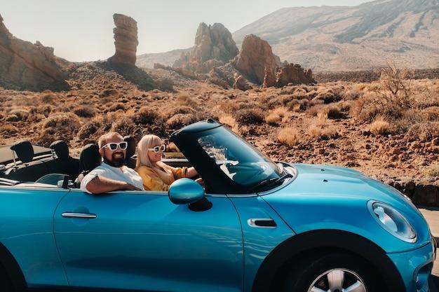 テネリフェ島への旅行でコンバーチブル車で眼鏡をかけている女性と男性。スペイン、カナリア諸島、テイデ火山のクレーター。