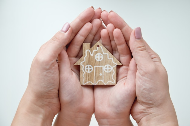 Женщина и ребенок держат в руках деревянный дом мама и дочь держат фигурку дома