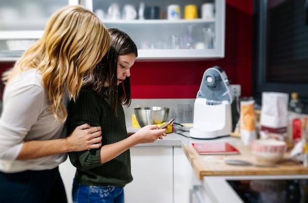 女性と母親が携帯電話を使ってキッチンでケーキを作る