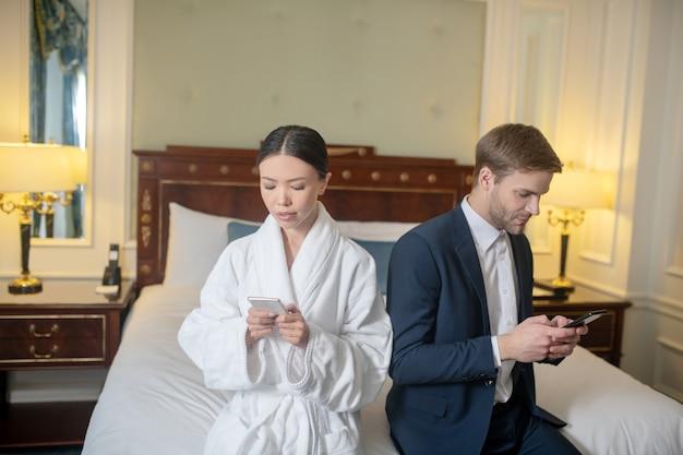 寝室でスマートフォンを使用している女性と男性
