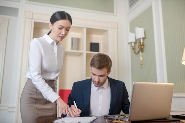 上司の書類提出を手伝う女性