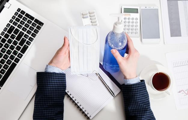 Женщина за письменным столом обрабатывает руки антибактериальным гелем. деловая женщина на рабочем месте с антисептической и защитной маской.