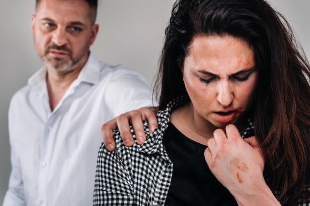 남편에게 구타를 당하는 여성은 뒤에 서서 그녀를 공격적으로 바라보고 있다. 가정 폭력
