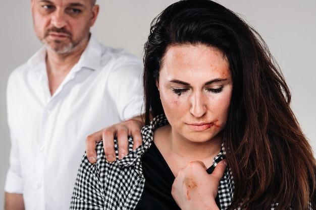 남편에게 구타를 당하는 여성은 뒤에 서서 그녀를 공격적으로 바라보고 있다. 가정 폭력.