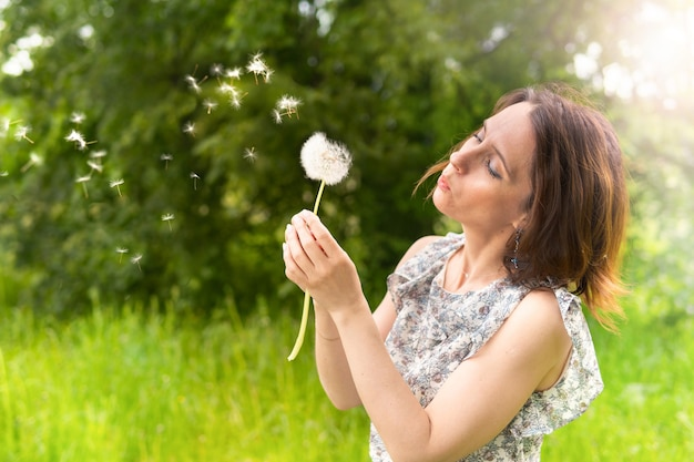 女性は自然の中でタンポポを吹きます。公園を歩いている幸せな女性。