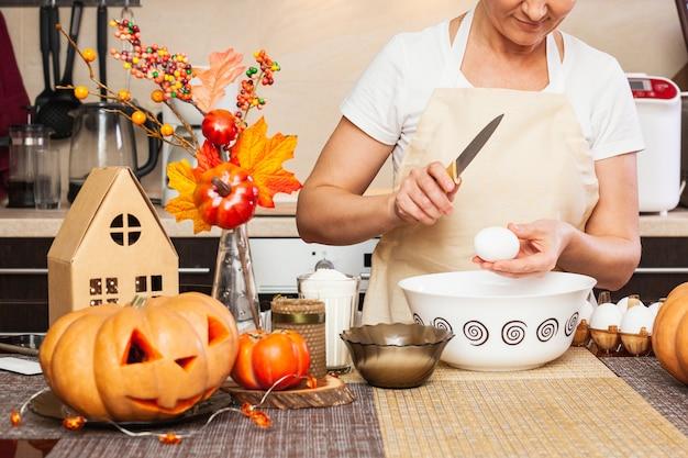 女性が秋の装飾が施されたキッチンでハロウィーンのクッキー生地をこねるために卵を割る。ハロウィン用のクッキー作り。