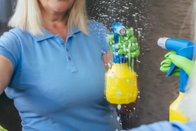 Женщина чистит зеркало моющим средством