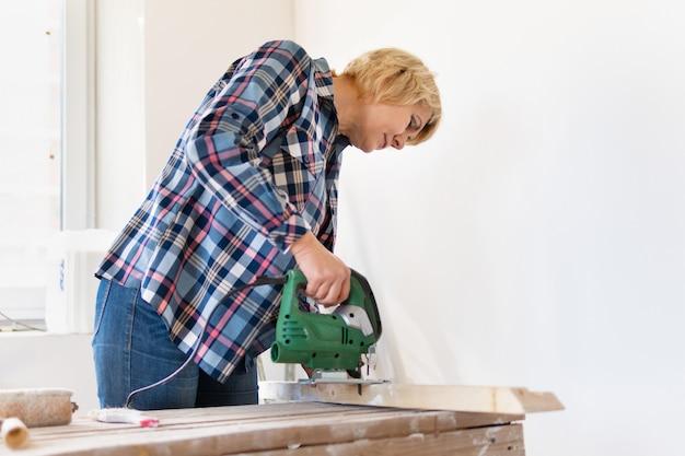 電気ジグソーを持った女性ビルダーが新しい建物のボードを切り落としました。中年女性がアパートの修理をします。