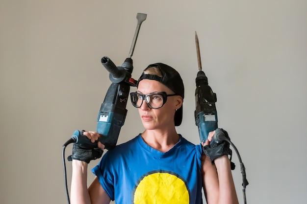 Женщина-строитель с двумя дреалами в руках. для любых целей.
