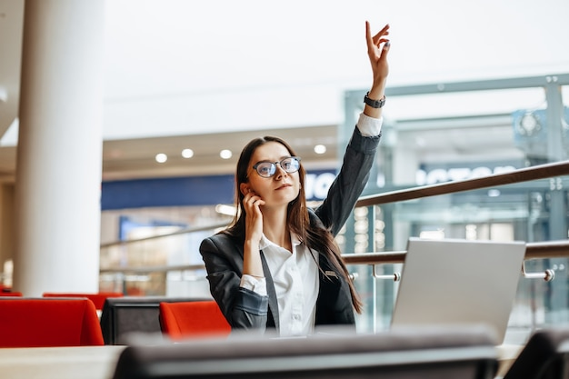 Женщина звонит коллеге, машет рукой на встречу. девушка работает на ноутбуке на рабочем месте. успешная бизнес-леди создает стартап и принимает решения.