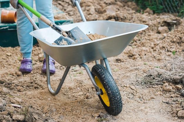 한 여성이 여름 별장에서 모래가 든 정원 수레를 나르고 있습니다.
