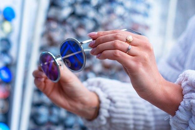 여자는 안경 쇼케이스의 배경에 대해 보호 선글라스를 선택합니다.
