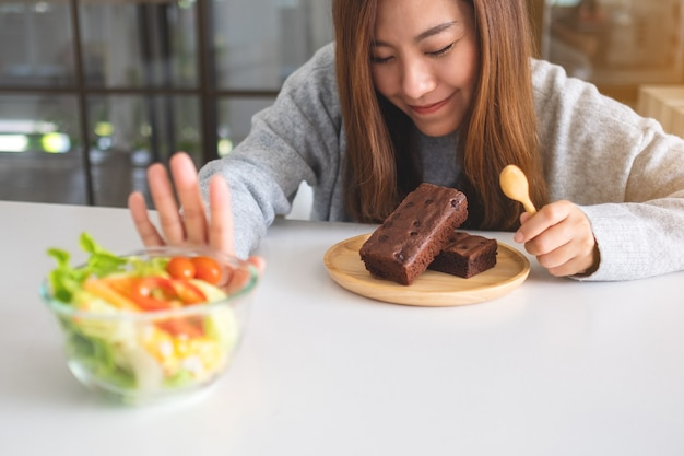 브라우니 케이크를 선택하고 식탁에 있는 야채 샐러드를 거부하는 손짓을 하는 여성