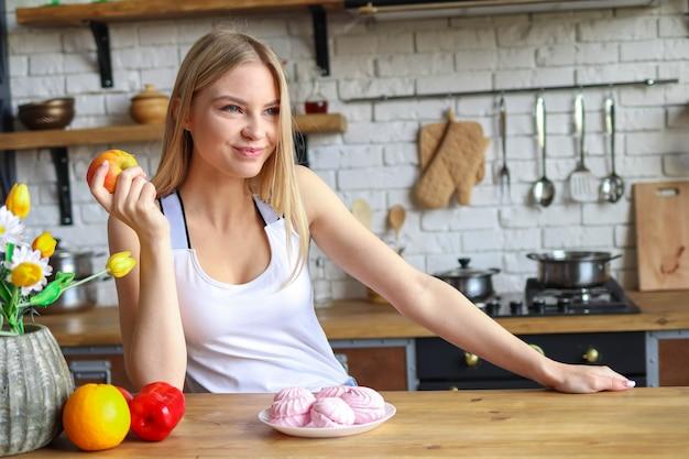 健康的な食生活のコンセプトであるお菓子ではなくリンゴを選んだ女性
