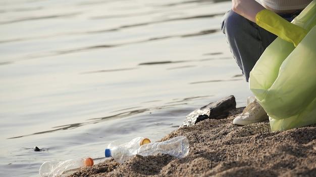 Женщина убирает мусор у озера. молодая женщина кладет пустые пластиковые бутылки в мешок для мусора. крупный план, 4k uhd.
