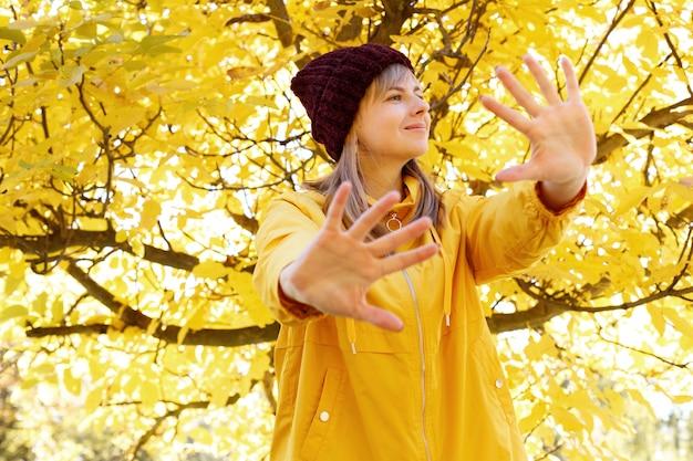 黄色い紅葉を背景に手を閉じる女性