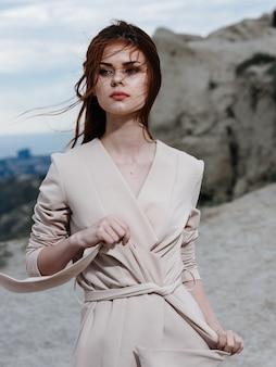 한 여성이 바위 근처 산에서 야외에서 온갖 종류의 옷을 코딩합니다.