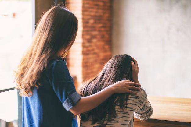 悲しい友達を慰め、励ましている女性