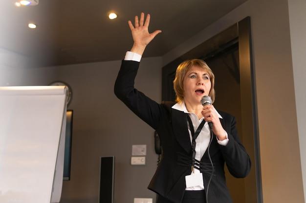 한 여성이 비즈니스 센터에서 교육을 실시하고 있습니다. 비즈니스 스타일의 플립 차트 보드에서 코칭하는 중년 여성.