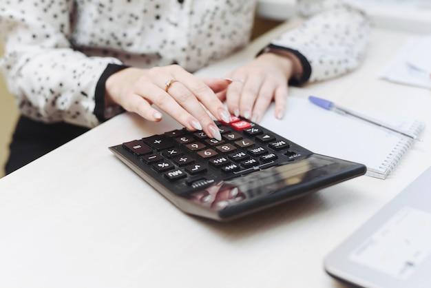 女性は計算機のコスト、収益、費用を考慮します。家計の分配。ビジネスウーマンは会計に従事しています