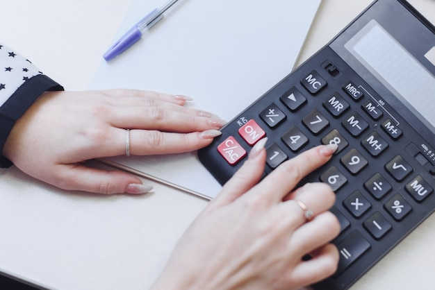 女性は、計算機のコスト、収益、費用を考慮します。家計の分配。ビジネスウーマンは会計に従事しています