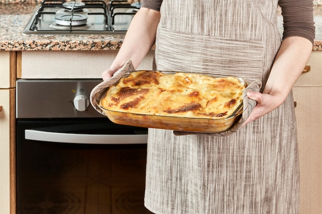 Женщина-повар достает из духовки горячую лазанью, свежеиспеченную с плавленым сыром и натертую на терке на ее кухне.