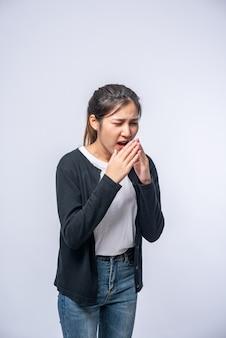 咳をして口を手で覆っている女性
