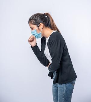 Женщина кашляет и прикрывает рот рукой