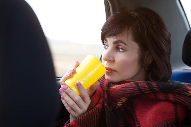 毛布で覆われた女性が車に乗って窓の外を眺め、温かい飲み物を飲む