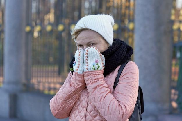 サマーガーデンの格子を背景に、凍った顔をウールのミトンで両手で覆う女性