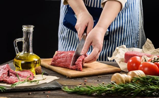 한 여성이 쇠고기 조각을 스테이크로 자릅니다. 고기를 절단하는 요리사의 손 클로즈업.