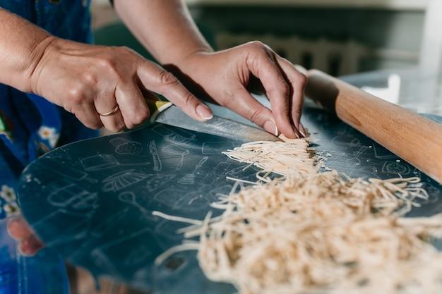 Женщина режет домашнюю лапшу на кухне