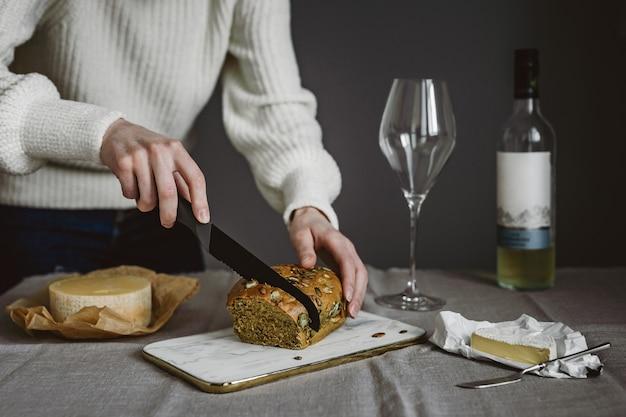 パン、数種類のチーズ、ワイングラス、白ワインのボトルを切る女性。横型ライフスタイル写真