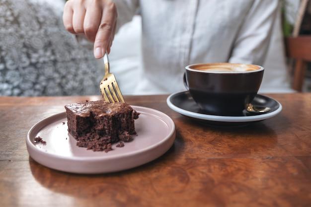 カフェの木製テーブルにコーヒーカップとフォークでブラウニーケーキを切る女性