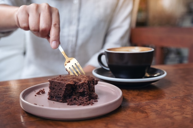 카페에서 나무 테이블에 커피 컵과 포크로 브라우니 케이크를 절단하는 여자