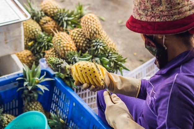 Женщина режет ананас на вьетнамском рынке