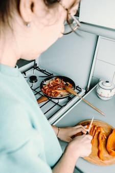 Женщина режет ножом перец над деревянной круглой тарелкой, готовя на сковороде на кухне