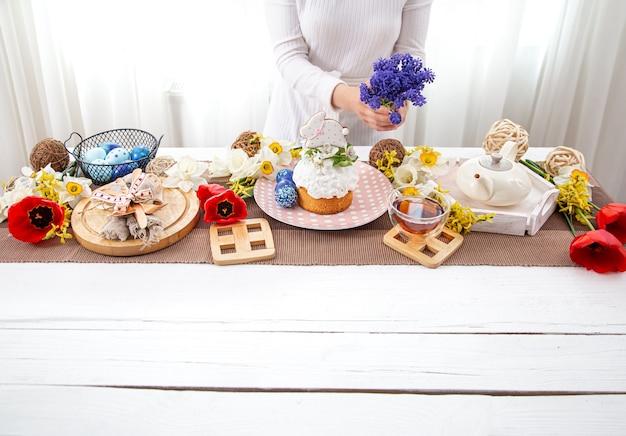 여자는 꽃으로 쟁기질로 테이블을 장식합니다. 부활절 휴가 개념.