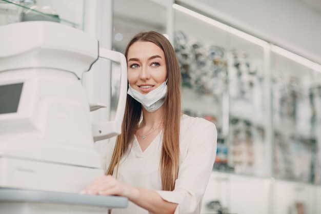 Женщина-врач и пациент делают офтальмологический рефрактометр проверяют зрение.