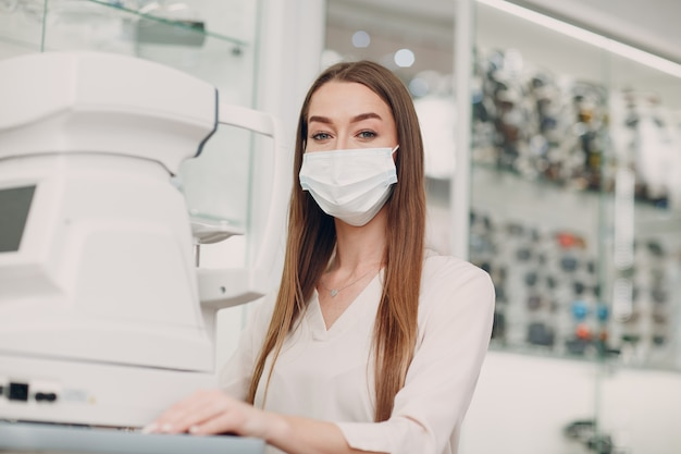 Женщина-врач и пациент с рефрактометром офтальмологический рефрактометр проверяют зрение