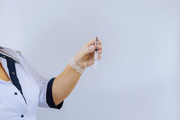 白い背景の上の薬とラテックス手袋を着用して注射器を持っている女性医師の手
