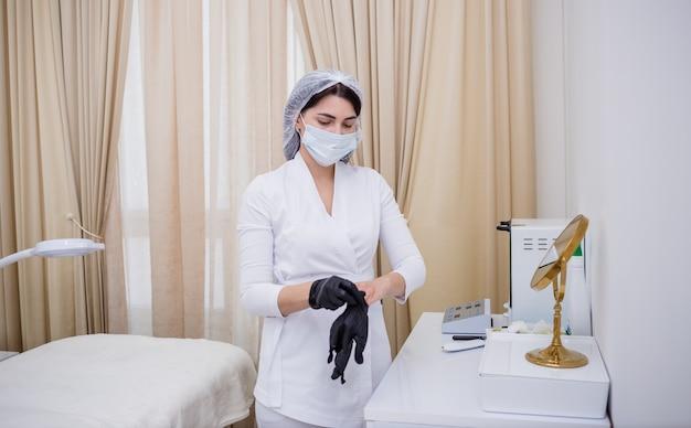 白い制服を着た女医がオフィスで黒い手袋をはめている。個人用保護具