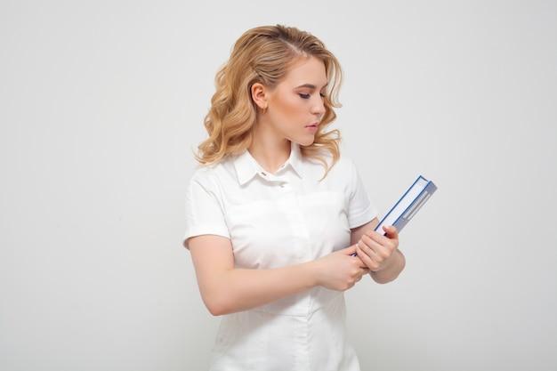 Женщина-врач с книгой, в медицинской форме на белой стене. понятие медицинского образования, высшего образования, чтения книг и профессии врача.